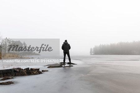 Man on rocks in frozen lake in Lotorp, Sweden