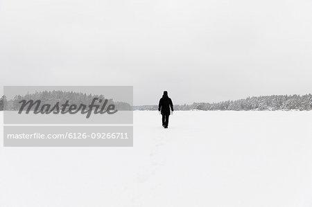 Woman wearing black walking on snow covered Stora Skiren lake in Lotorp, Sweden