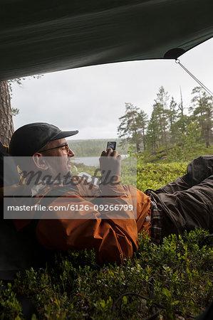 Man using smart phone in tent