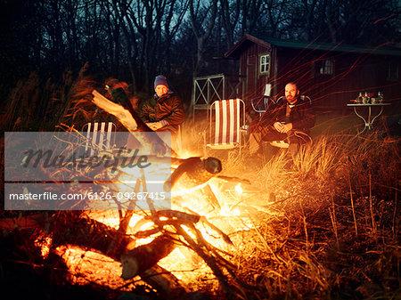 Men sitting by bonfire at sunset