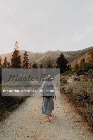 Young woman in maxi dress wearing backpack walking along rural road, rear view, Mineral King, California, USA