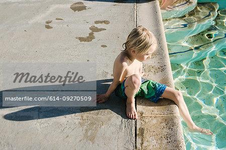 Boy sitting by swimming pool
