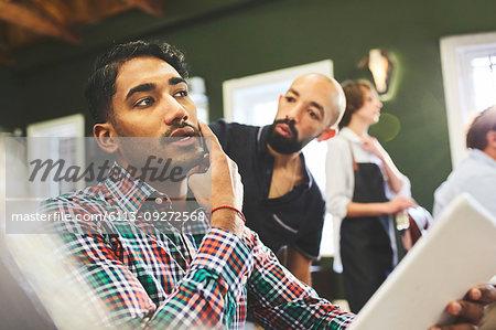 Male customer and barber talking in barbershop