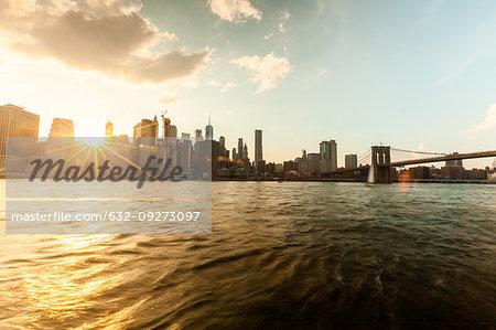 Manhattan city skyline and Brooklyn Bridge at sunset