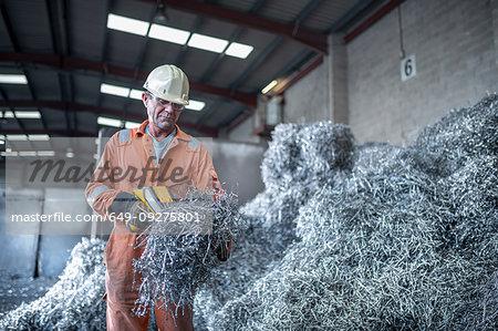Worker testing titanium swarf in titanium recycling plant