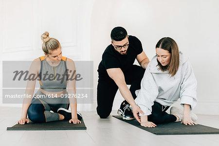 Fitness instructor teaching women stretching legs in studio