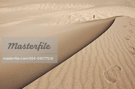 Hiker exploring sand dunes, Great Sand Dunes National Park and Preserve, Colorado, USA