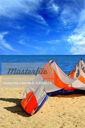 Big kite for kite surfing lying on a sandy beach