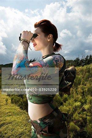 Attractive tattooed Caucasian woman standing looking through binoculars in Maui, Hawaii, USA.