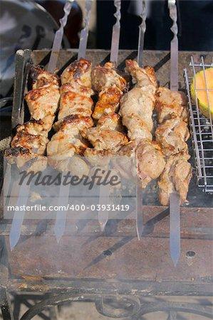 Appetizing shish kebab on metal skewers outdoors at picnic