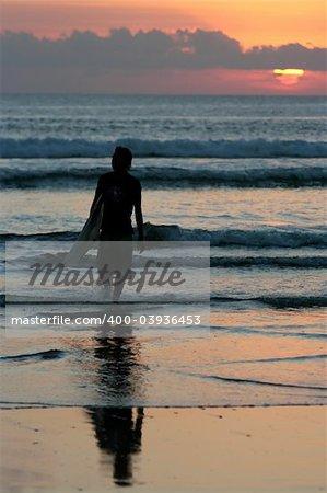 Surfer at sunset, Kuta beach, Bali