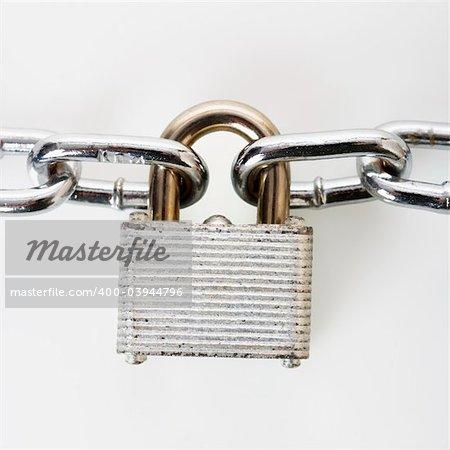 Metal padlock locked to chains.