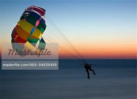 Two women parasailing against a dawn sky