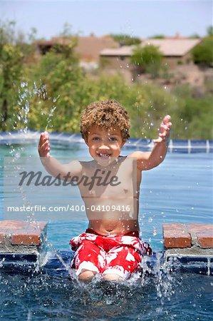 Cute young boy splashing in a swimming pool