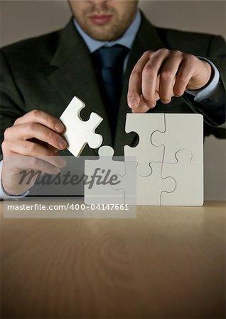 A businessman making a puzzle.