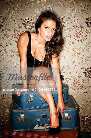 Woman sitting on vintage suitcases adjusting her high heel shoe