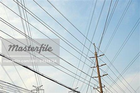 Mesh of power lines against blue sky