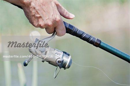 Closeup of a fisherman hand holding a fishing rod