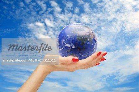 hand and earth (globe) over blue sky