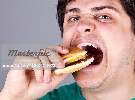 Cute boy eating hamburger. Studio shot.