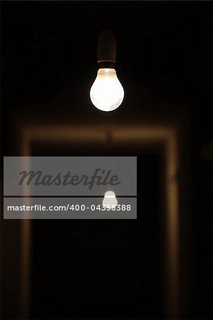 Bare light bulbs in dark underground hallway.