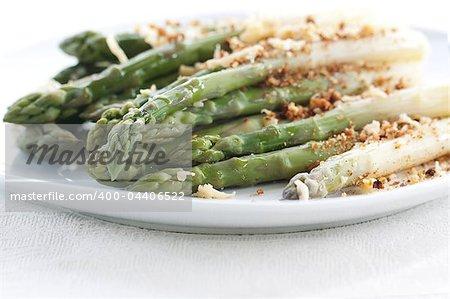 Asparagus gratin on white plate on white background