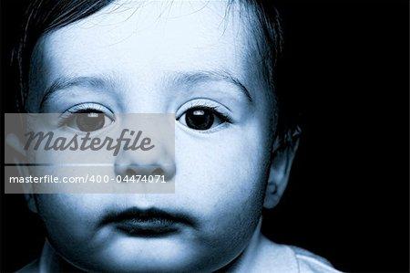 baby portrait over black background blue tone
