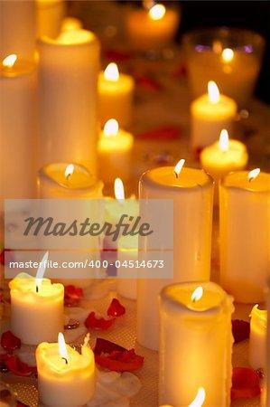 Many burning celebratory candles on a dark background