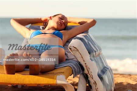 Bikini Girl with boogie board sleeping on the chair