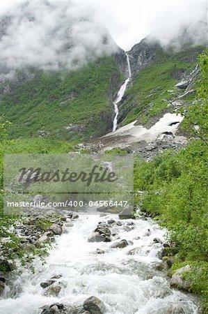 Raging river among the rocks, waterfall, fog, cloudy