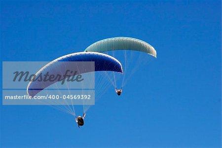Paraglider soaring in a blue sky