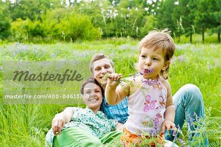 Lovely toddler eating flower, smiling parents in back