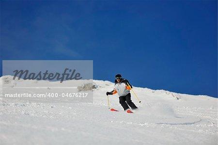 skier free ride downhill at winter season on beautiful sunny day