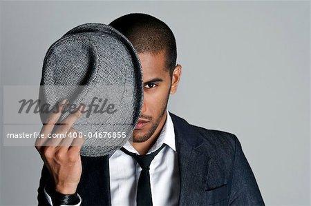 Man peeks from behind his fedora in studio