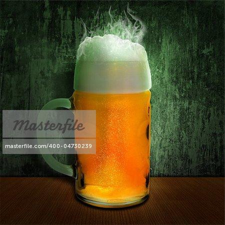 cool beer mug at wooden table over grunge wall