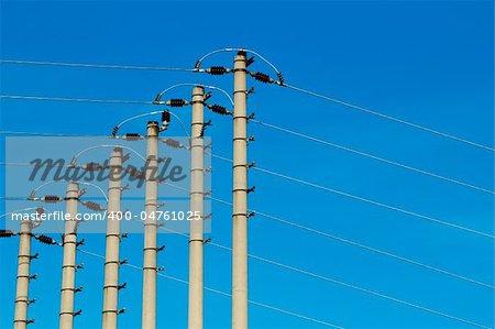High-voltage pole against a blue sky