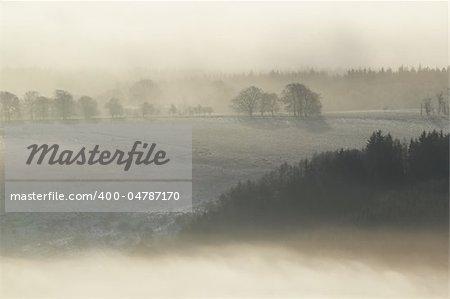 Frozen sunlit Scottish winter landscape rising above the mist