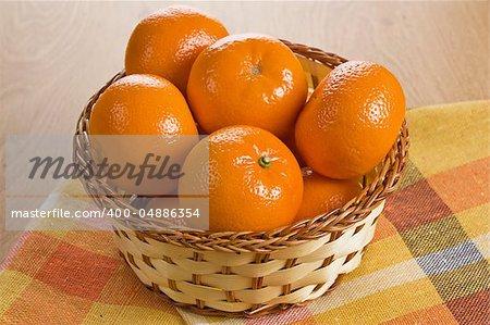 Ripe fresh tangerine in wicker basket on wooden background
