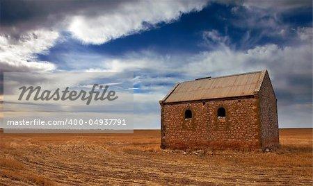 An old farm building in a sprawling field
