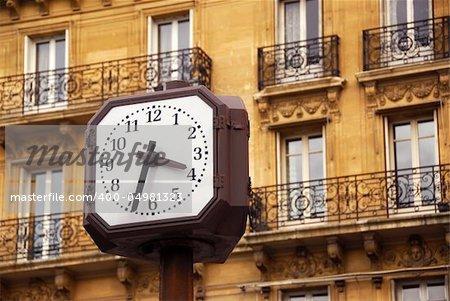 Public clock in Paris on background of old apartment building