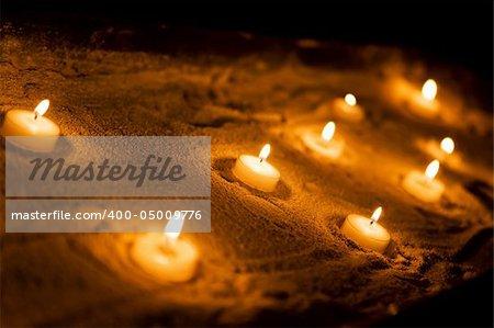 Wax sacred candles on a sand