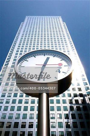 A skyscraper, street clocks and a blue sky