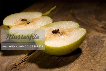 autumn fresh pears cut  in half over old wood board