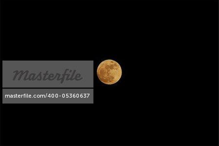 big orange full moon shines in the night