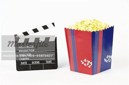 Movie clapper board and box of popcorn over white