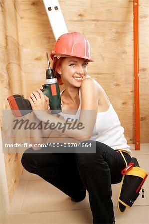 caucasian woman as worker wearing red protective helmet