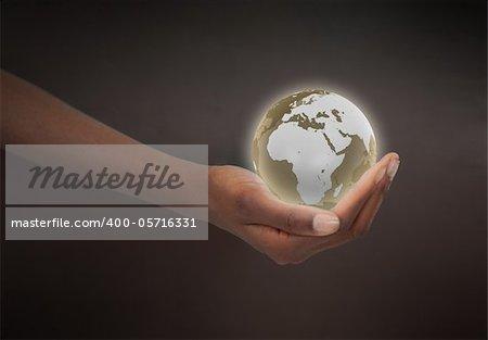 Feminine hand holding a planet globe against a dark background