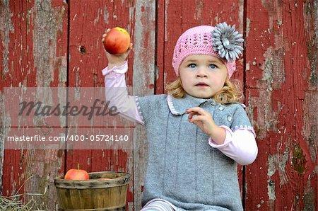 Little girl ready to throw an apple.