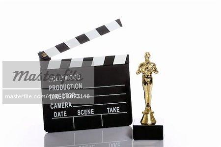 Movie clapper board and fake Oscar over white