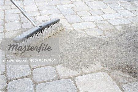 Broom Sweeping Locking Sand Into Backyard Patio Pavers